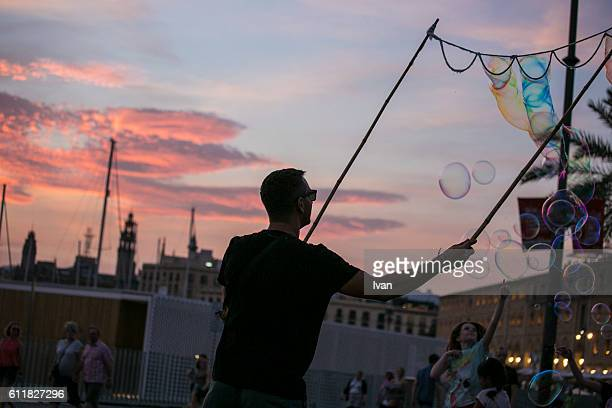 Low Angle View Of Silhouette Man Blowing Giant Bubble From Wand During Sunset with Dramatic Sky
