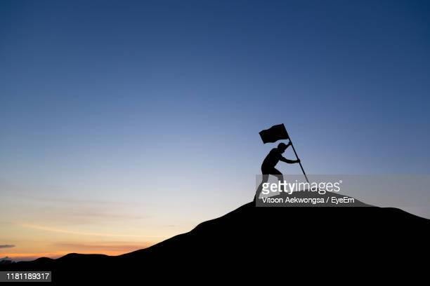 low angle view of silhouette man holding flag on mountain against clear sky during sunset - summit stock pictures, royalty-free photos & images