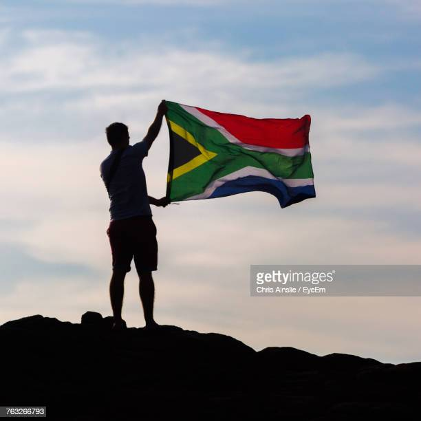 low angle view of silhouette man holding south african flag standing against sky - south african flag stock photos and pictures