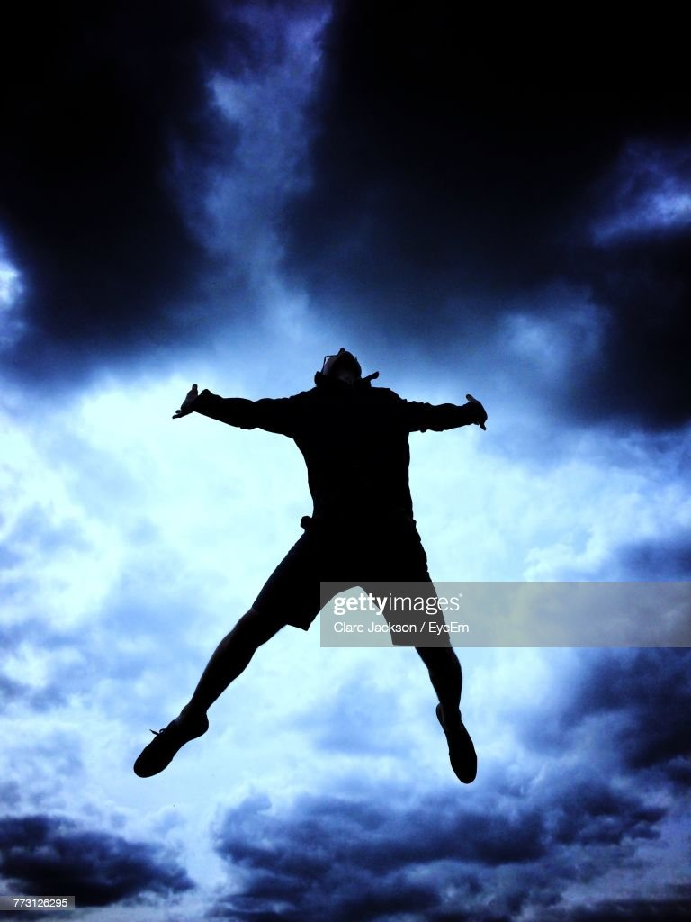 Low Angle View Of Silhouette Man Jumping Against Sky : Photo