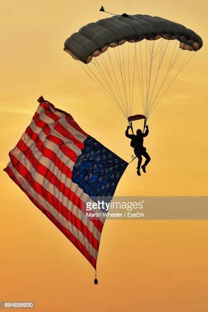 Low Angle View Of Silhouette Man Paragliding With American Flag