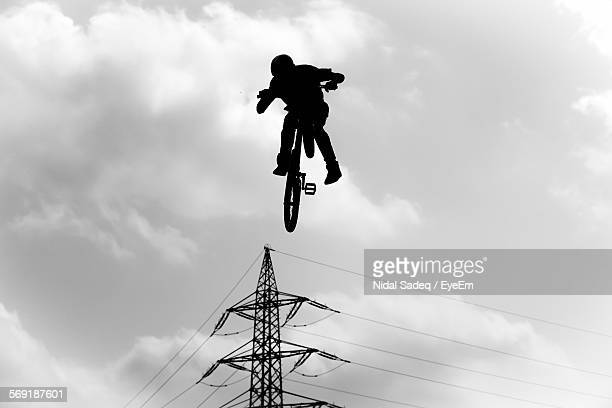 Low angle view of silhouette man performing stunt on bicycle