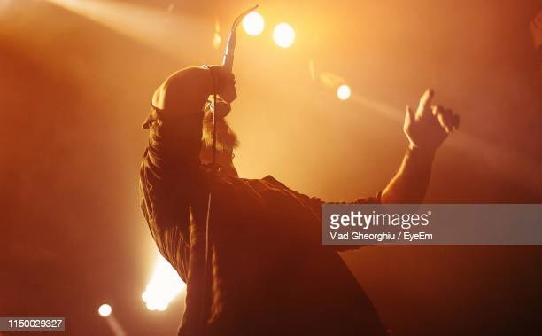 low angle view of silhouette man singing in music concert - chanteur photos et images de collection