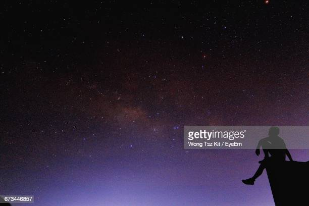 Low Angle View Of Silhouette Man Sitting On Cliff Against Star Field