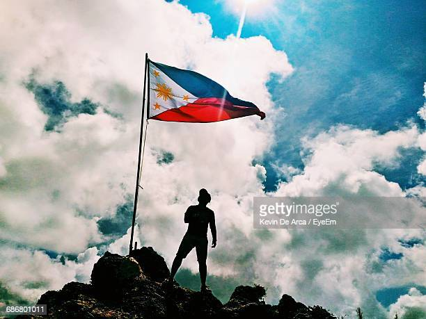 Low Angle View Of Silhouette Man Standing By Philippines Flag On Mountain Against Cloudy Sky