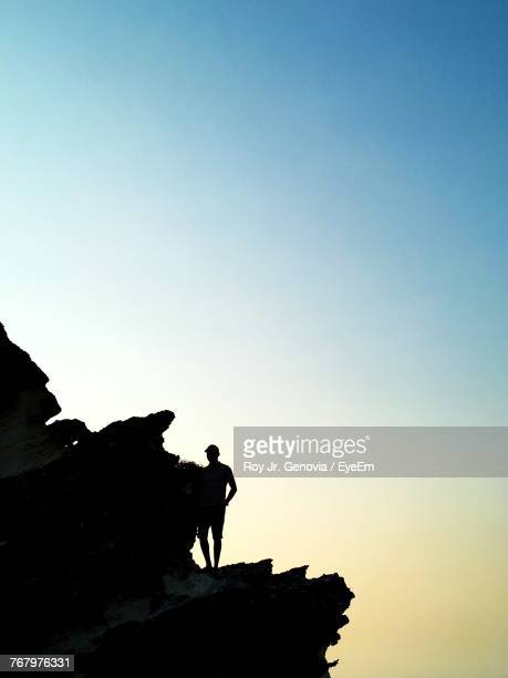 low angle view of silhouette man standing by rock against clear sky - genovia imagens e fotografias de stock
