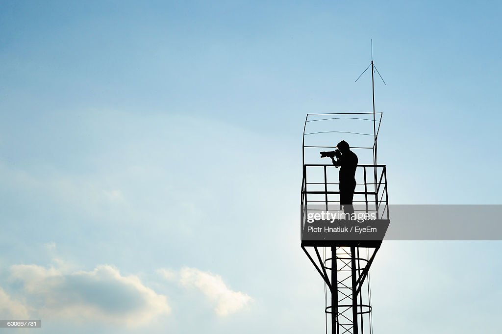 Low Angle View Of Silhouette Man Standing In Lookout Tower Against Sky : Stock Photo