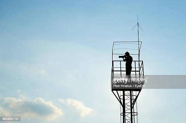 low angle view of silhouette man standing in lookout tower against sky - piotr hnatiuk photos et images de collection