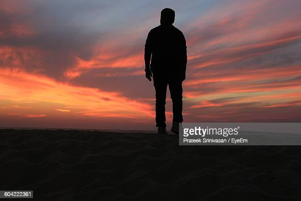 Low Angle View Of Silhouette Man Standing On Field Against Sky During Sunset