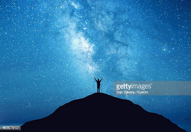 Low Angle View Of Silhouette Man Standing On Mountain Against Blue Star Field At Night