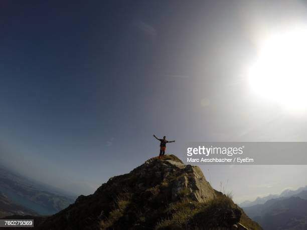 Low Angle View Of Silhouette Man Standing On Mountain Against Sky