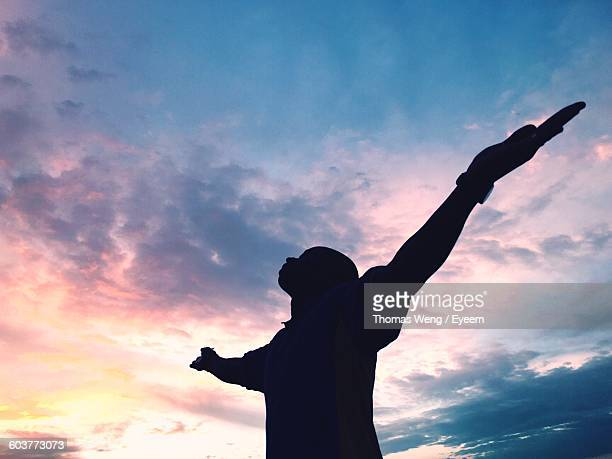 Low Angle View Of Silhouette Man With Arms Outstretched Against Sky During Sunset
