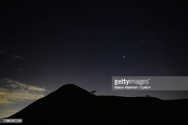 low angle view of silhouette mountain against sky at night - martinelli stock pictures, royalty-free photos & images