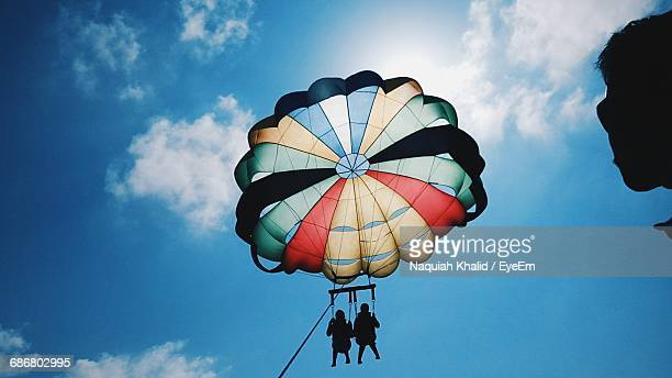 Low Angle View Of Silhouette People Enjoying Paragliding Against Sky