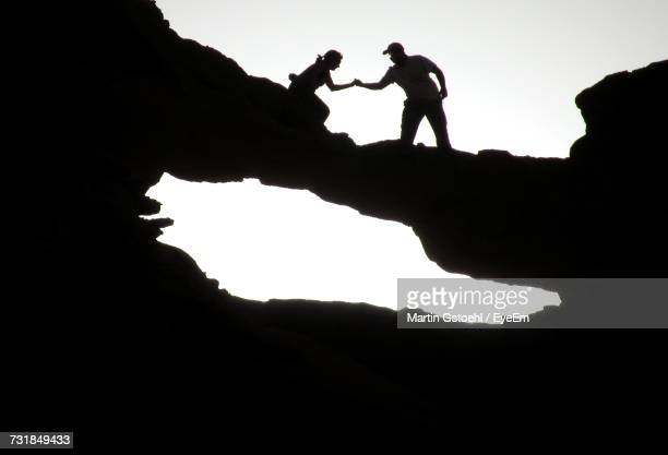 Low Angle View Of Silhouette People On Cliff Against Clear Sky