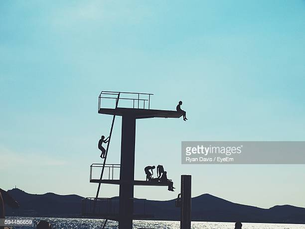 Low Angle View Of Silhouette People On Diving Platform On Sea Against Sky