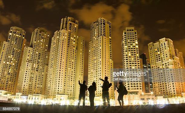 low angle view of silhouette people standing against illuminated buildings - four people stock pictures, royalty-free photos & images