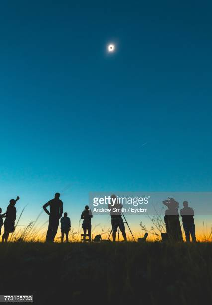 Low Angle View Of Silhouette People Standing On Field Against Clear Sky At Night