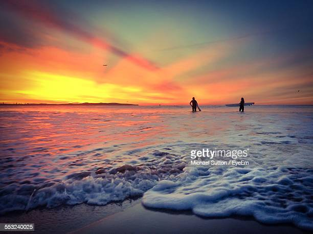 Low Angle View Of Silhouette People With Surfboard Standing On Beach