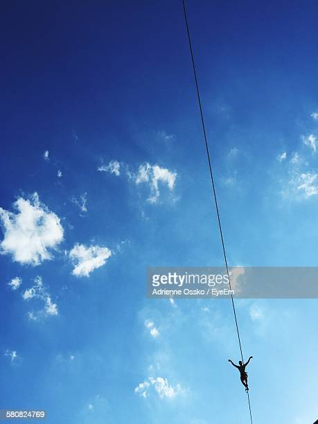 Low Angle View Of Silhouette Person Balancing On Slackline Against Blue Sky