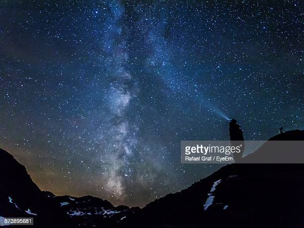 Low Angle View Of Silhouette Person On Mountain Against Sky At Night