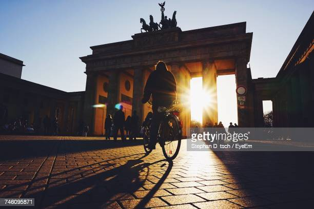 Low Angle View Of Silhouette Person Riding Bicycle On Footpath By Brandenburg Gate