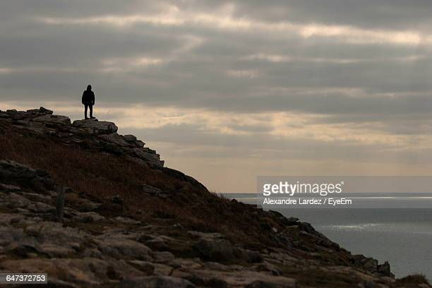 Low Angle View Of Silhouette Person Standing On Mountain Against Cloudy Sky