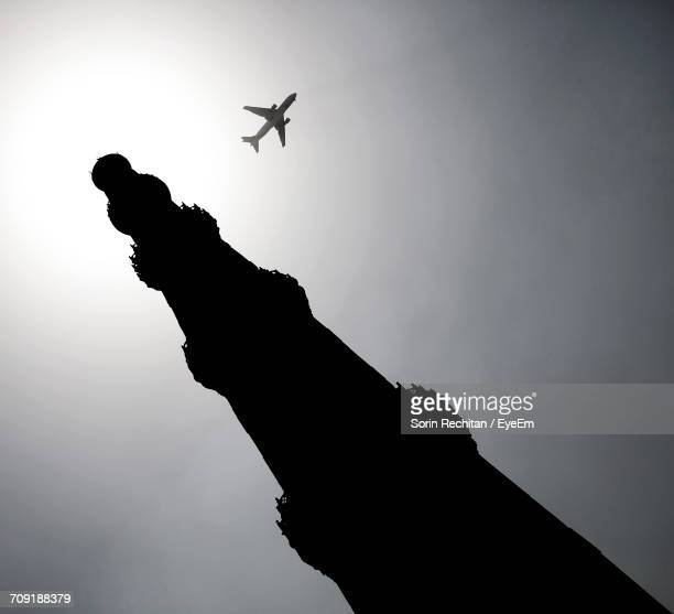 Low Angle View Of Silhouette Qutb Minar Against Airplane Flying In Clear Sky