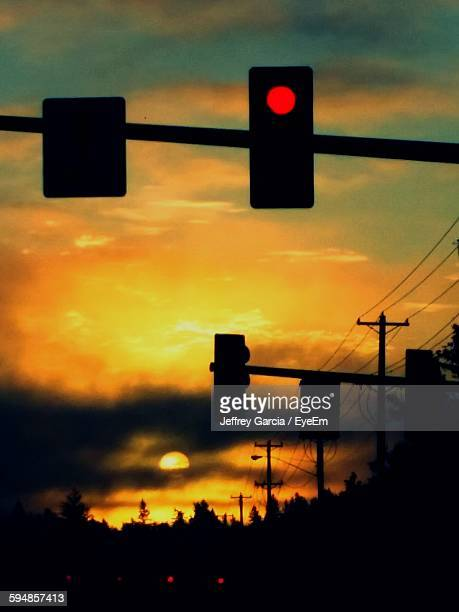 Low Angle View Of Silhouette Road Signal Against Sky