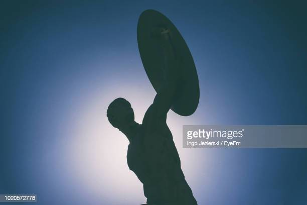 low angle view of silhouette statue against clear blue sky - shield stock pictures, royalty-free photos & images