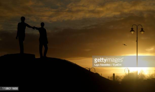 low angle view of silhouette statues against cloudy sky during sunset - statue stock pictures, royalty-free photos & images