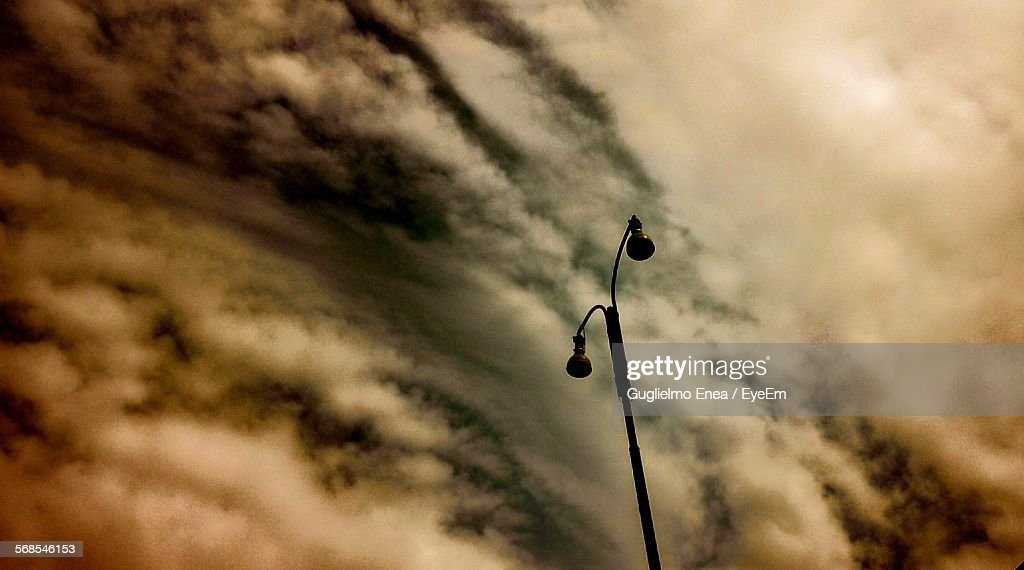 Low Angle View Of Silhouette Street Light Against Cloudy Sky : Foto de stock