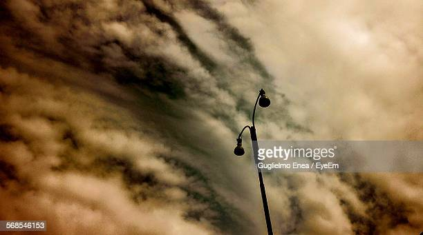 Low Angle View Of Silhouette Street Light Against Cloudy Sky