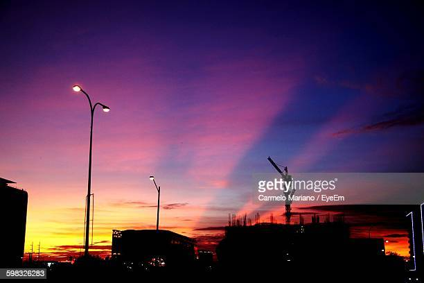 low angle view of silhouette street lights and buildings against sunset sky - carmelo ストックフォトと画像