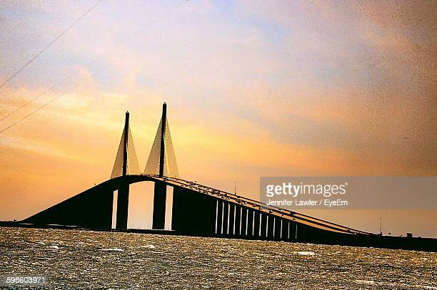 low angle view of silhouette sunshine skyway bridge in front of sea during sunset - sunshine skyway bridge stock photos and pictures
