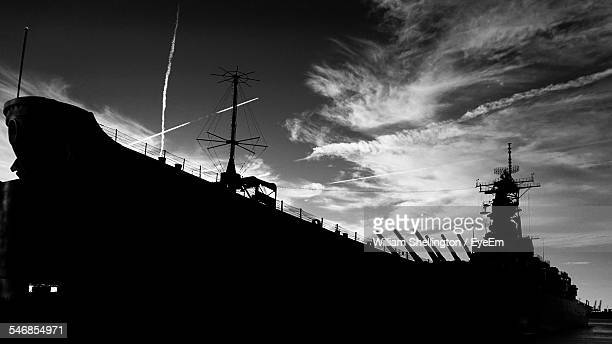 low angle view of silhouette us navy ship against cloudy sky - military ship stock pictures, royalty-free photos & images