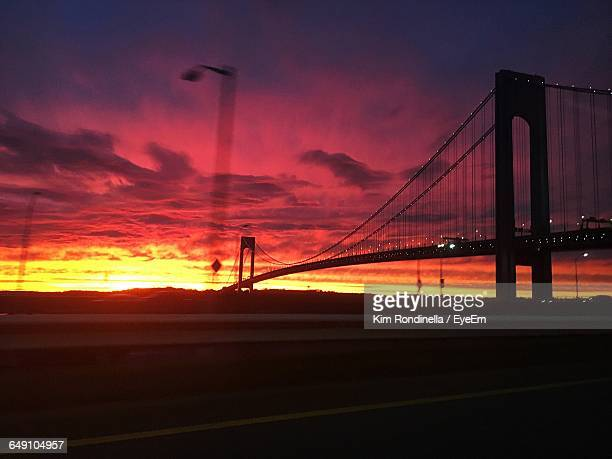 Low Angle View Of Silhouette Verrazano-Narrows Bridge Against Cloudy Orange Sky During Sunset