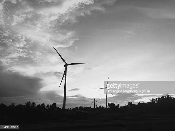 low angle view of silhouette windmills on field at sunset - american style windmill stock pictures, royalty-free photos & images