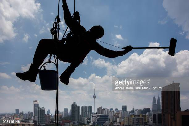 low angle view of silhouette window washer working against sky - window cleaning stock photos and pictures
