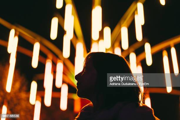 Low Angle View Of Silhouette Woman Against Illuminated Lights At Night