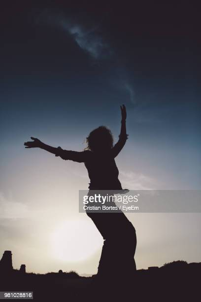 Low Angle View Of Silhouette Woman Dancing Against Sky During Sunset