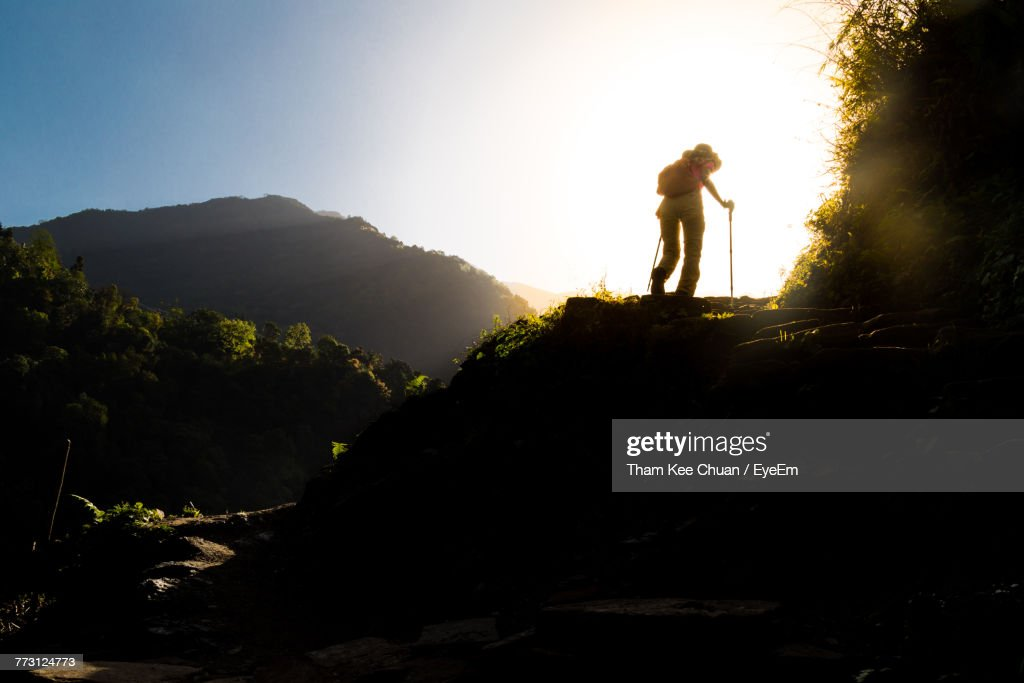 Low Angle View Of Silhouette Woman Hiking On Mountain Against Sky : Photo