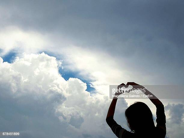 Low Angle View Of Silhouette Woman Making Heart Shape With Hands Against Cloudy Sky