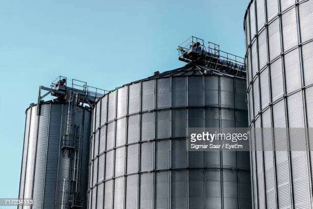 low angle view of silos against clear blue sky - fuel storage tank stock photos and pictures