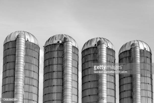 low angle view of silos against sky - silo stock photos and pictures