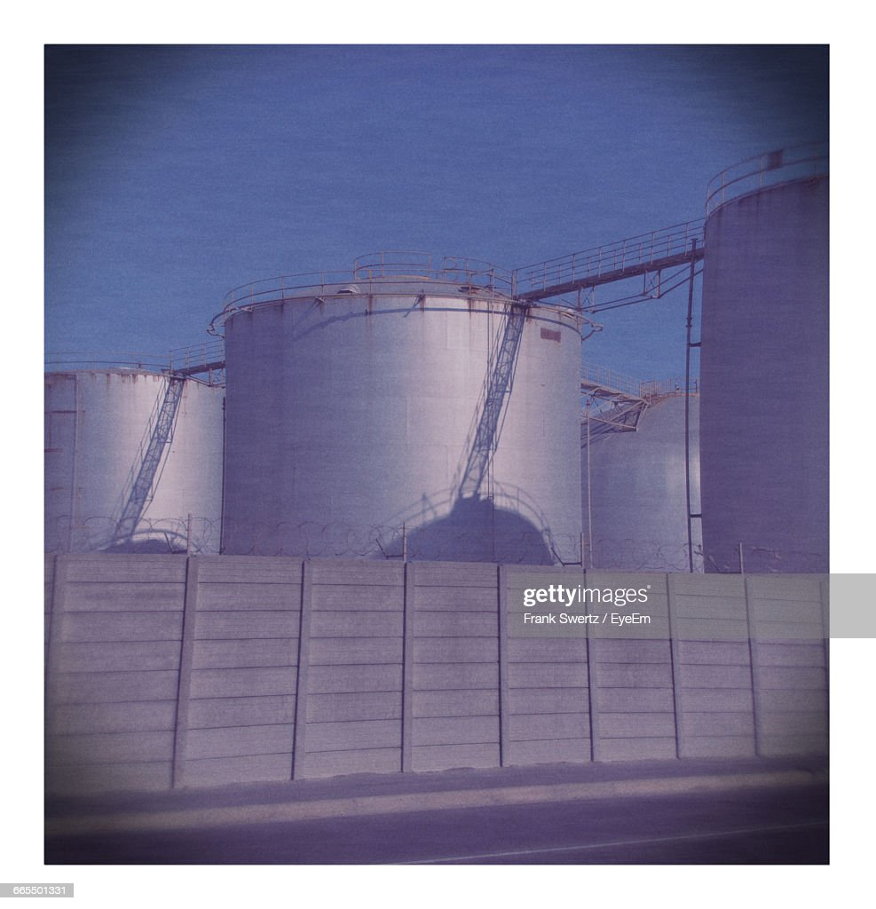 Low Angle View Of Silos At Factory Against Sky : Stock-Foto