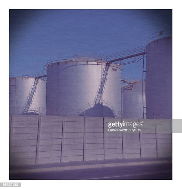 low angle view of silos at factory against sky - frank swertz stock-fotos und bilder