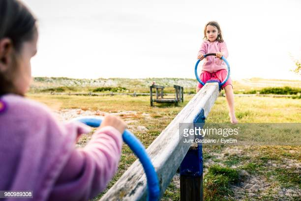 low angle view of sisters playing on seesaw - biciancola foto e immagini stock