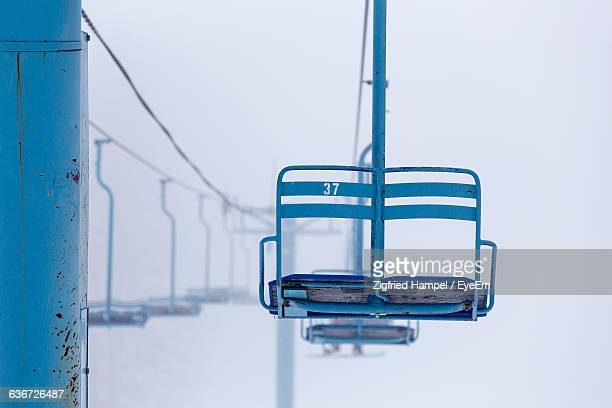 low angle view of ski lift over snow covered field - ski lift stock pictures, royalty-free photos & images