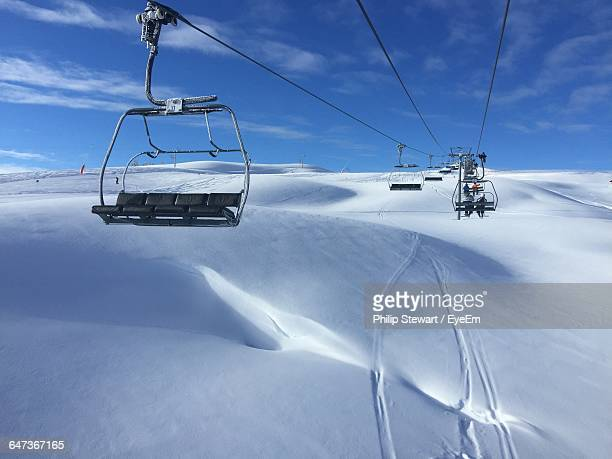 Low Angle View Of Ski Lift Over Snowy Field Against Cloudy Sky During Sunny Day